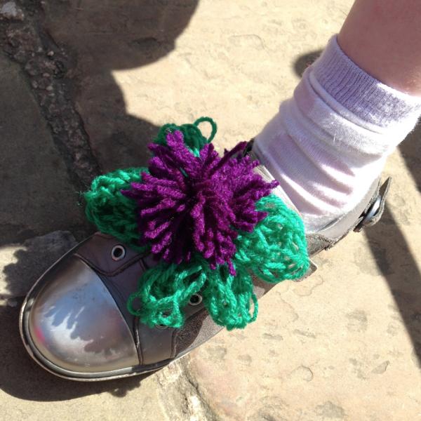 Finger knitted flower on shoe