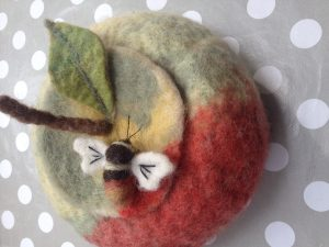 Needle felted bee brooch on a felted apple