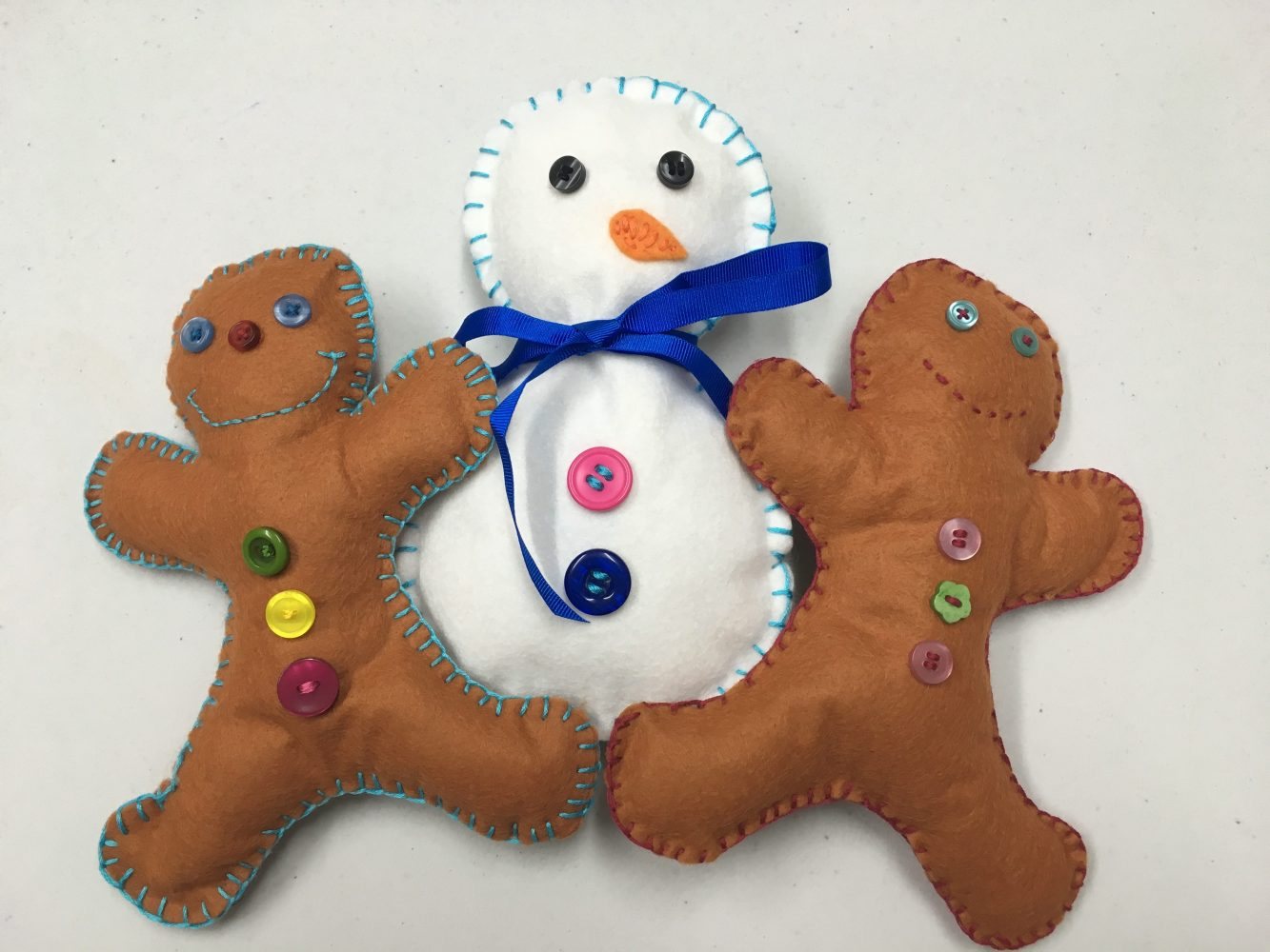 hand sewing kids gingerbread men and snowman